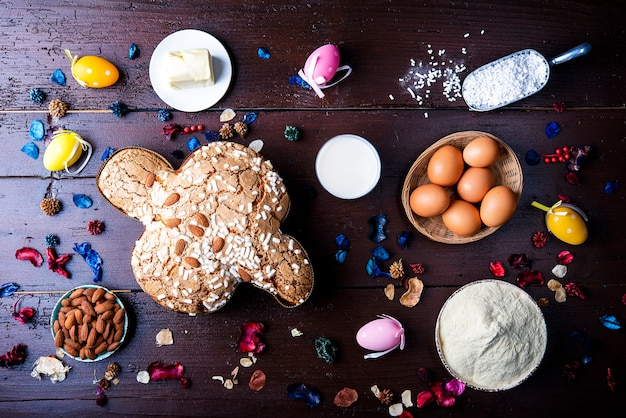 Easter dove bread (colomba pasquale) typical italian cake for easter holiday with amond and icing on a rustic wooden table flat lay
