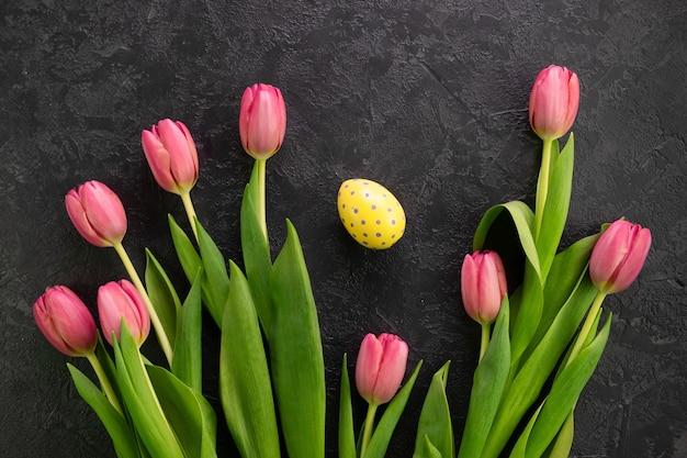 Пасхальное яйцо и розовые тюльпаны на темном бетонном фоне