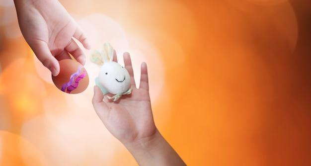 ボケ味の背景に子供の手でイースターエッグとウサギ。イースターコンセプトの背景。