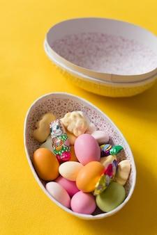 黄色のbackgorundにキャンディーとチョコレートスカンジナビアの伝統を持つイースターエッグボックス