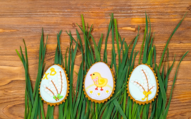 Печенье пасхальное яйцо, покрытое глазурью на деревянном фоне с зеленой травой