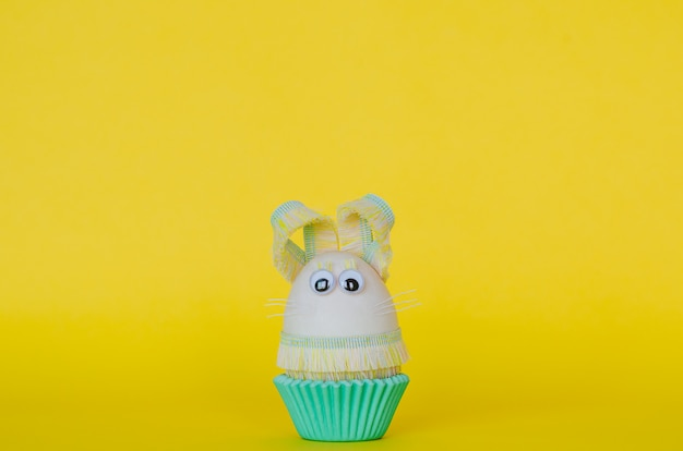 Easter egg decorate as bunny on colorful cupcake paper cup