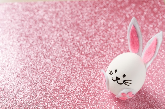 Easter egg decorated as cute bunny on the shiny glitter pink background.
