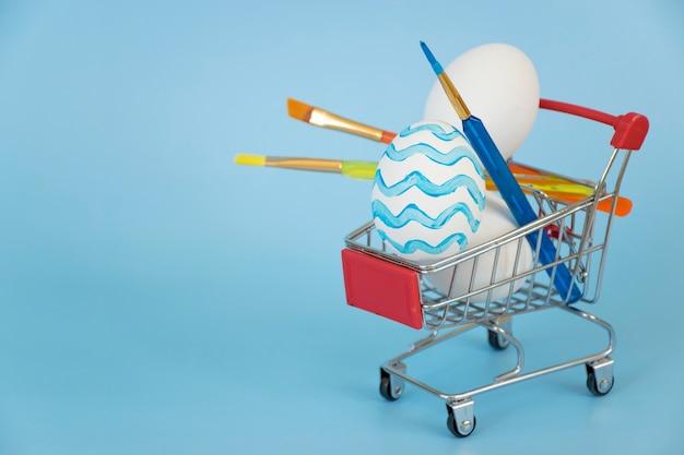 ショッピングカート内の他の白い卵や絵筆と青い波で飾られたイースターエッグ