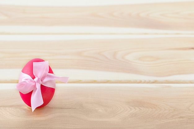 Easter egg decorated with pink bow on a wooden table
