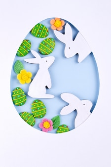 Easter egg frame made of paper, sugar candy eggs, bunny on blue background