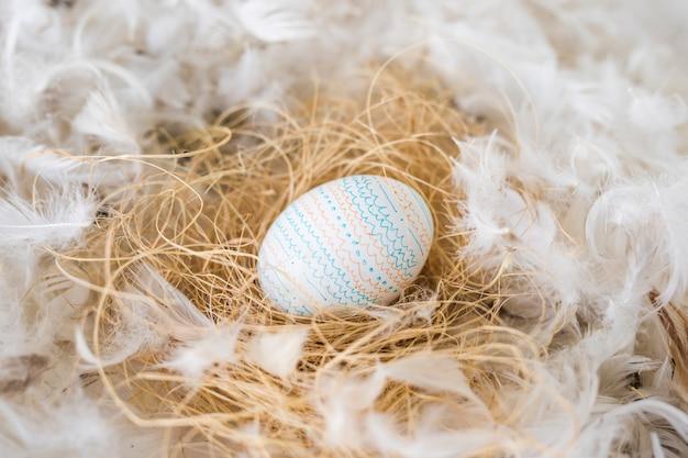 Easter egg on hay between heap of quills