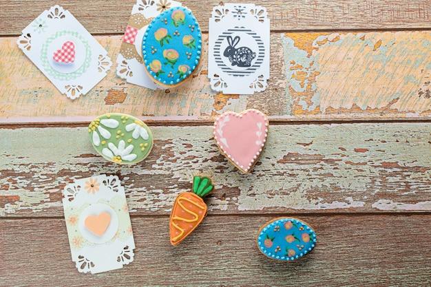 ハートとウサギのカードに囲まれた木製のテーブルにイースターエッグ、ハート、ニンジンのクッキー。