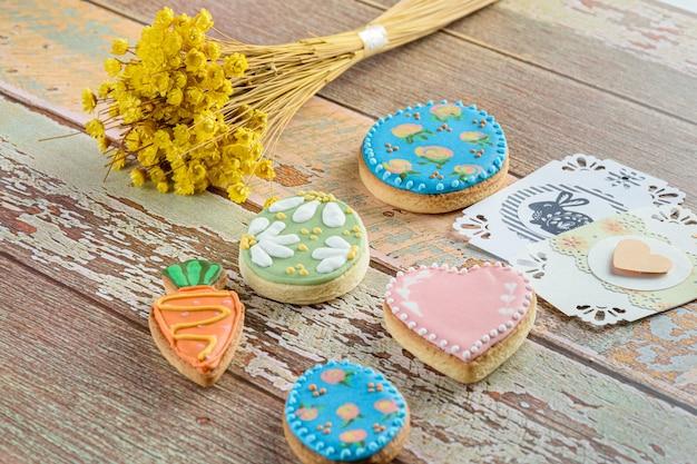 ハートとウサギのカードに囲まれたイースターエッグ、ハート、ニンジンのクッキー。