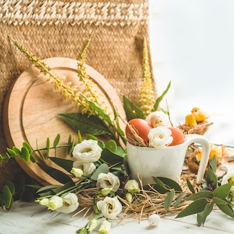 窓の近くの花の装飾が付いている巣のイースターエッグ。ウズラの卵。ハッピーイースターのコンセプト
