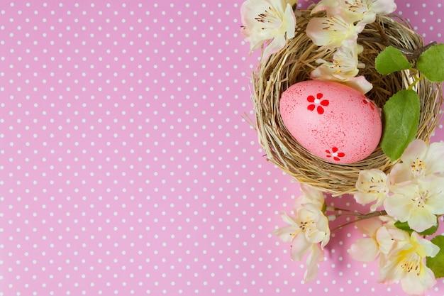 ピンクの水玉模様の背景にわらの巣と開花枝のイースターエッグ。上面図、テキスト用のスペースのあるフラットレイ。
