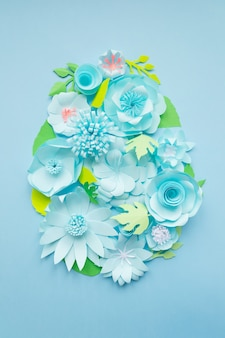 Easter egg made of paper flowers on blue. cut from paper.