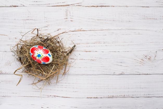 Easter egg over nest on wooden background