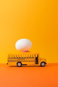 テキスト用のコピースペースを備えた黄色のスクールバスのイースターエッグ。イースターコンセプトの背景に合わせたヴィンテージカラー。