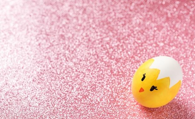 부활절 달걀 핑크 반짝이 배경에 재미있는 얼굴을 가진 노란 병아리로 그린.