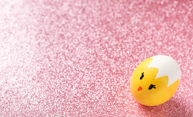 Easter egg painted as yellow chick with funny face on the pink glitter background.