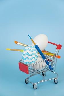 青い波で描かれたイースターエッグと他の白い卵と青のショッピングカートの絵筆