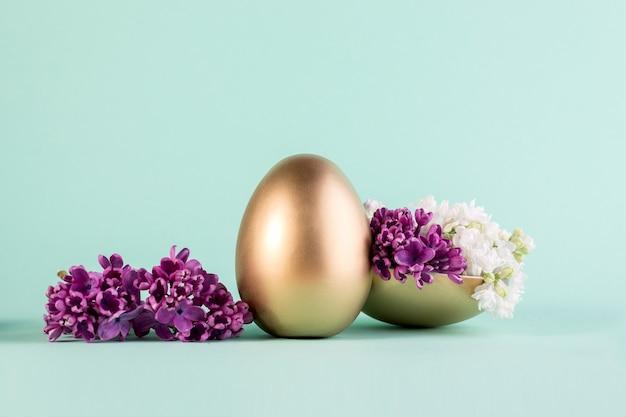 Пасхальное яйцо в золотом цвете декорировано фиолетовыми цветами сирени.