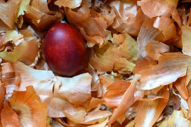 イースターエッグはタマネギの殻を描いた。皮をむいた玉ねぎを使った古い自然環境にやさしい方法に従って卵を着色する