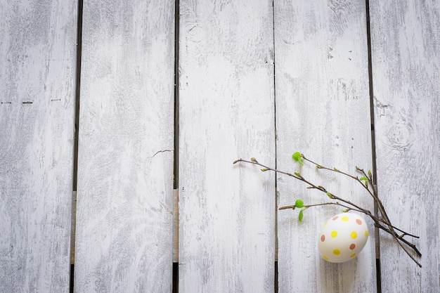 Easter egg and twigs with young leaves on rustic wooden planks
