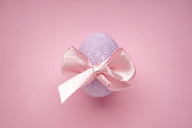 Пасхальное яйцо с бантом на розовой поверхности. вид сверху