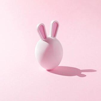 Пасхальное яйцо с ушками зайчика на розовом фоне. креативная пасхальная концепция.