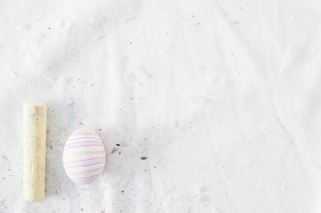 Easter egg with pattern near quills and chalk on textile