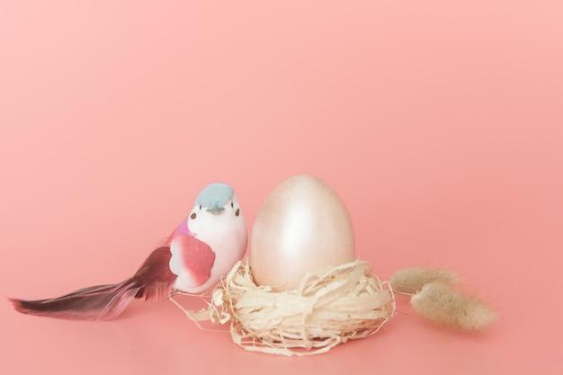 明るいピンクの背景にイースターエッグと鳥。