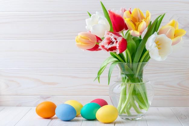 부활절 달걀과 나무 테이블, 꽃 정물화에 튤립 꽃다발. 휴일 개념.