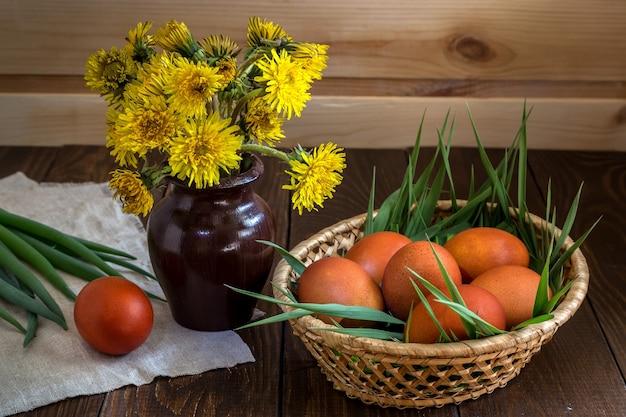 Пасхальные яйца и букет одуванчиков в вазе
