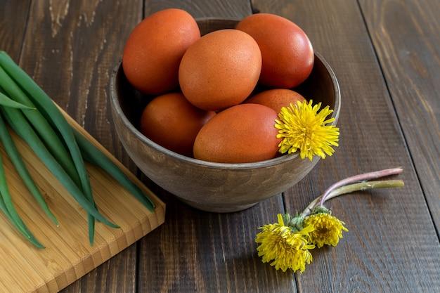 Пасхальные яйца и букет одуванчиков на деревянный стол