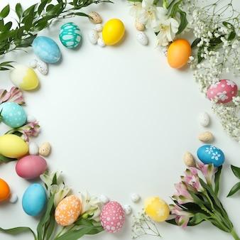 Пасхальные яйца и красивые цветы на белом фоне, место для текста