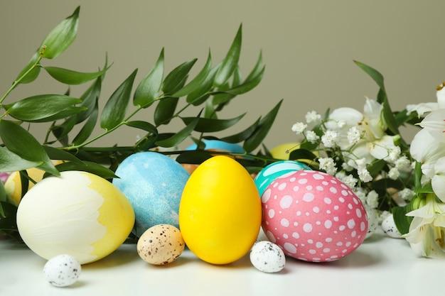 Пасхальные яйца и красивые цветы на белом столе