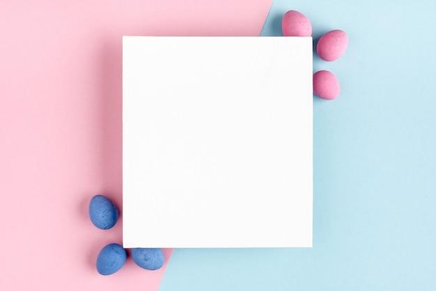 パステルブルーピンクの背景にイースターエッグと空白の白いキャンバス