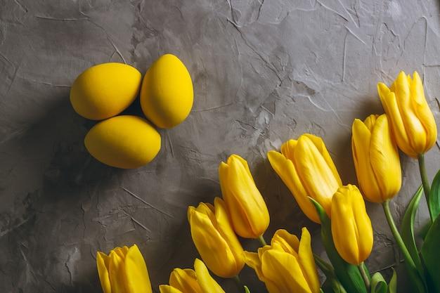 Пасхальные яйца и букет ярко-желтых тюльпанов на серой бетонной поверхности