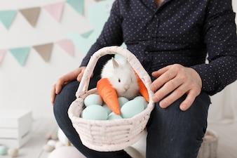 イースターの卵と人のラップのバスケットのウサギ。