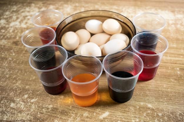 부활절을 준비하는 동안 흰색 삶은 달걀에 염료와 그림을 사용하는 어린이를 위한 테이블 위에 있는 부활절 달걀과 유색 액체 페인트