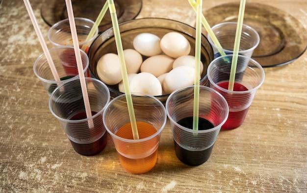 イースターの準備中に染料を使用し、白いゆで卵に絵を描く子供のためのテーブル上のイースターエッグと着色された液体塗料