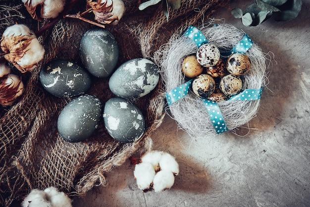 灰色の石にイースターエッグと綿の花。