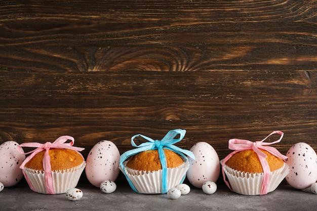 Пасхальные яйца и пасхальные кексы на деревянном фоне
