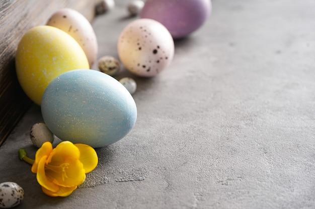 Пасхальные яйца и цветок на сером фоне