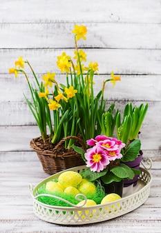 イースターエッグと明るい木製テーブルの花