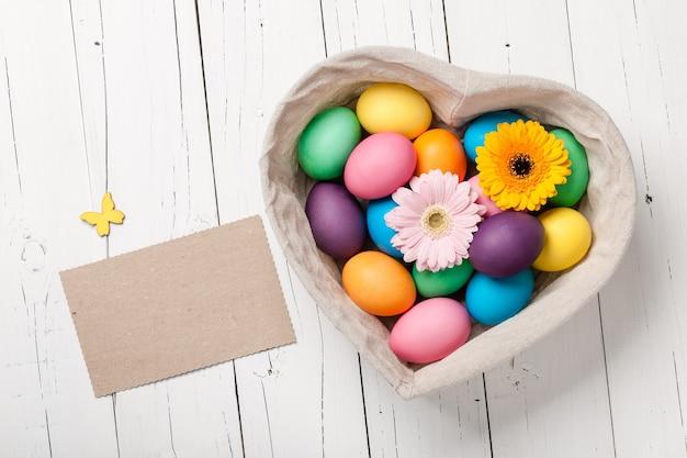 하트 모양의 바구니에 부활절 달걀과 거베라 꽃