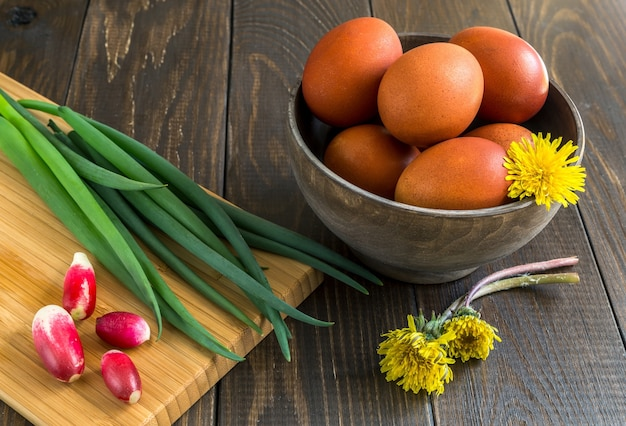 Пасхальные яйца и лук с редисом на столе