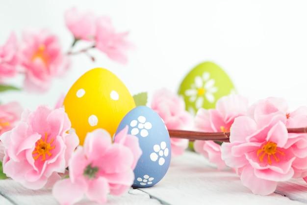 青い背景にイースターエッグとピンクの花の装飾。優しいトーンの写真