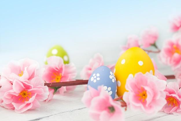 부활절 달걀과 파란색 바탕에 분홍색 꽃 장식. 부드러운 톤의 사진