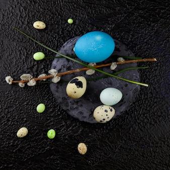 Пасхальные яйца и ветки вербы, стоящие на круглом сланцевом камне