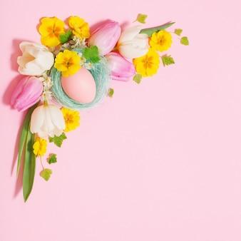 Пасхальные яйца и весенние цветы на розовой поверхности