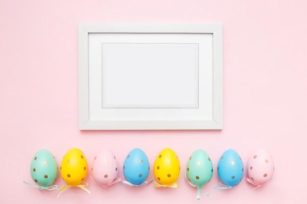 Пасхальные яйца и белая фоторамка на розовом