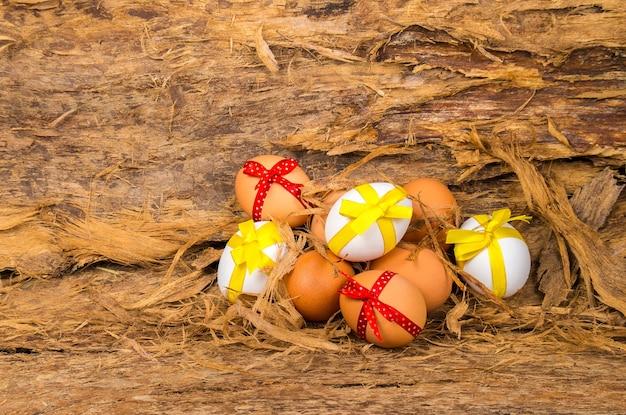 イースターエッグは木の樹皮に黄色と赤のリボンで飾られています